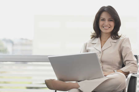 looking at camera: Hispanic businesswoman holding laptop
