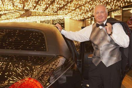 babyboomer: Senior man in tuxedo next to limousine