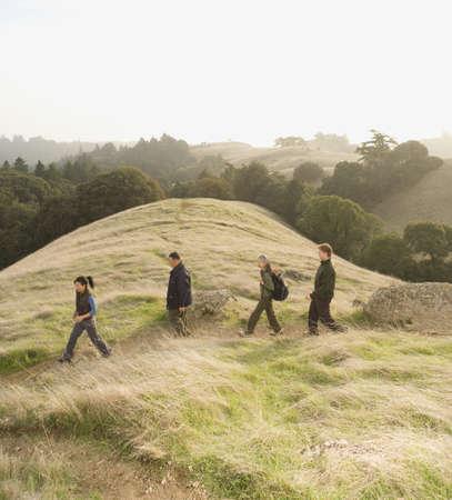 adventuresome: Multi-ethnic friends hiking on hillside