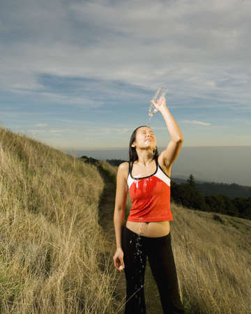 tugging: Asian woman pouring water over head on hillside