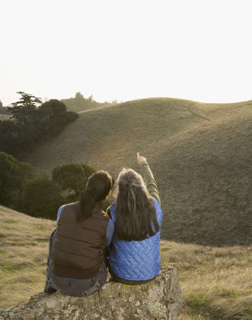 hindering: Two women pointing at hill in countryside LANG_EVOIMAGES