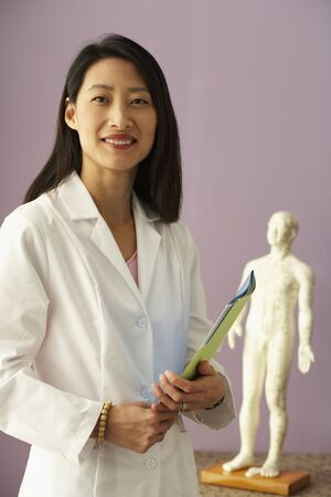 exactitude: Asian female doctor next to Acupuncture model LANG_EVOIMAGES