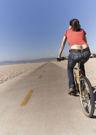 german ethnicity: Woman riding bicycle at beach