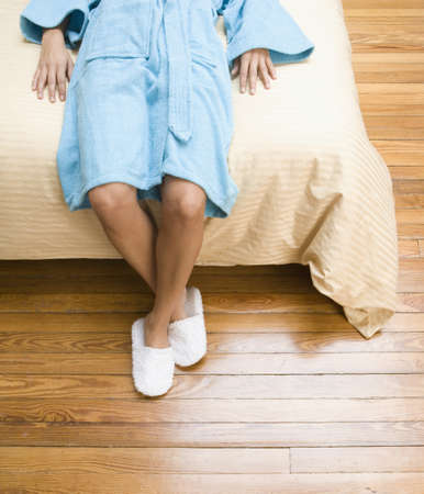 casualness: Woman laying on bed with feet on floor