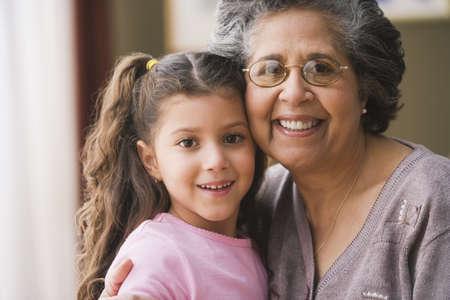 hispanic girl: Hispanic grandmother hugging granddaughter