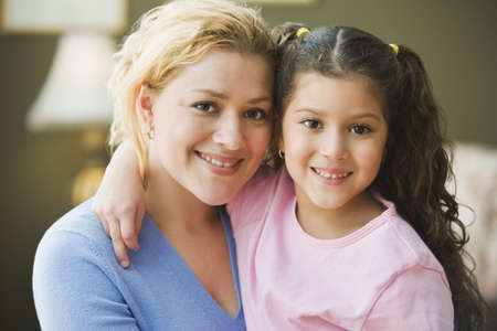 Hispanic mother and daughter hugging and smiling