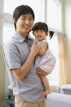 longshot: Asian father holding baby daughter LANG_EVOIMAGES