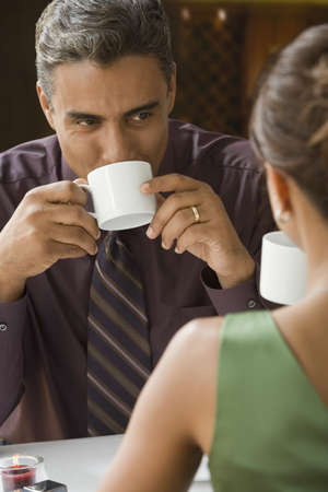 commercialism: Hispanic couple drinking coffee LANG_EVOIMAGES