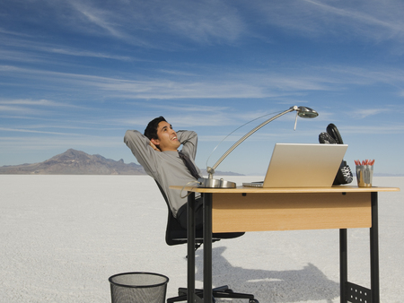 Hispanic businessman at desk on salt flats