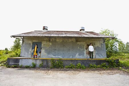 longshot: Asian couple standing on opposite sides of porch LANG_EVOIMAGES