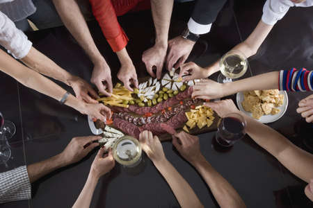 snacking: Multi-ethnic friends reaching for food at party LANG_EVOIMAGES