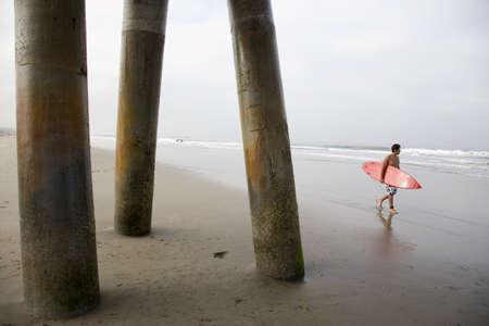 adventuresome: Hispanic man carrying surfboard LANG_EVOIMAGES