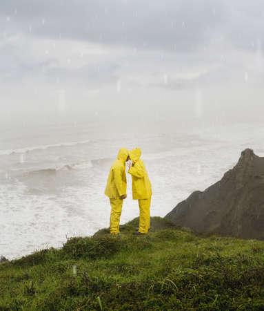 german ethnicity: Hispanic couple in rain gear kissing on cliff