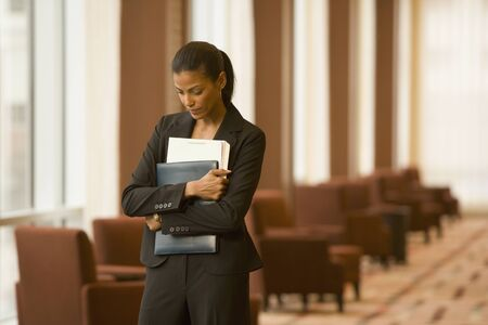 relishing: African businesswoman holding paperwork in hotel lobby