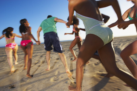 Multi-ethnic group of friends running on beach