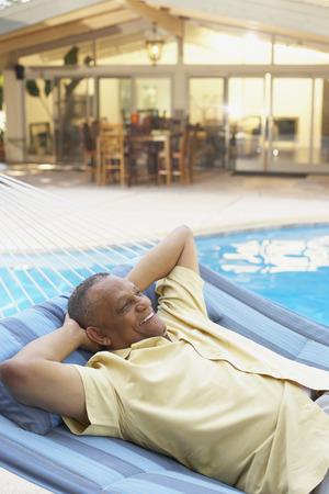bathingsuit: African man laying in hammock at poolside