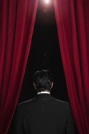milepost: Hispanic man in tuxedo standing between red curtains LANG_EVOIMAGES