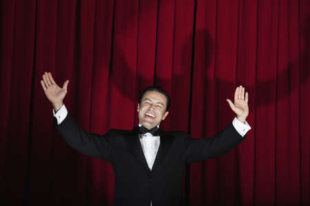 flowergirl: Hispanic man in tuxedo singing with arms outstretched onstage