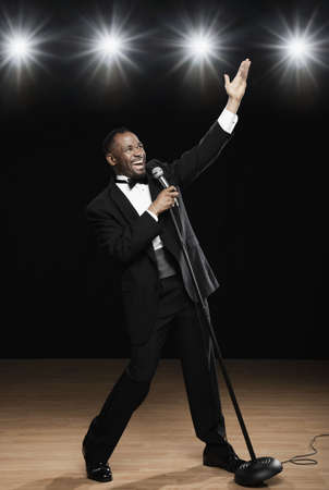 onstage: African American man in tuxedo singing into microphone onstage