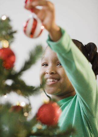 African American girl putting ornament on Christmas tree