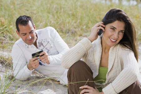 Hispanic couple talking on cell phones at beach
