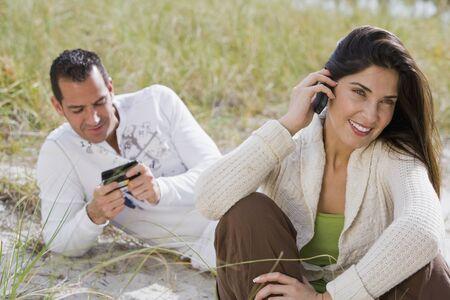 talker: Hispanic couple talking on cell phones at beach