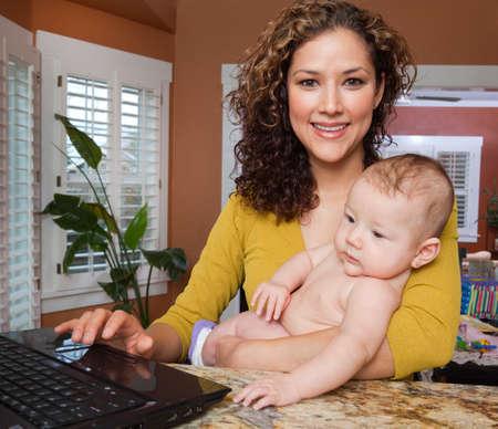 latina america: Hispanic woman holding baby and typing on laptop LANG_EVOIMAGES
