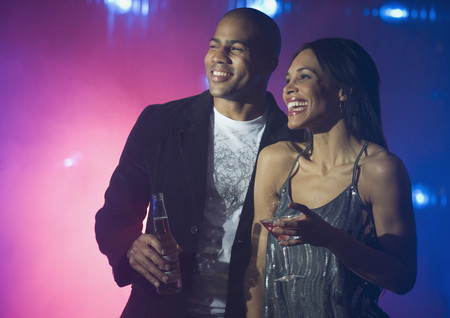 Boyfriend and girlfriend holding drinks at nightclub