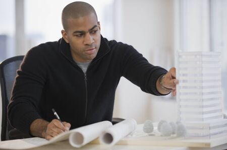architect drawing: African American architect working on building model LANG_EVOIMAGES