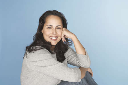 enquiring: Hispanic woman smiling with head in hands LANG_EVOIMAGES