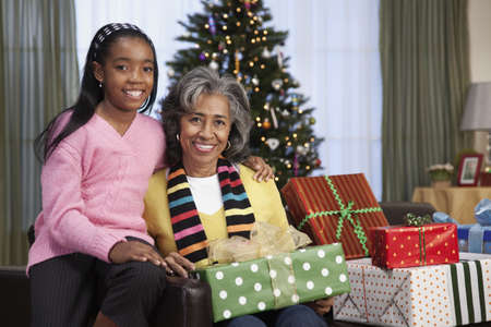 generation gap: African girl giving grandmother Christmas gift