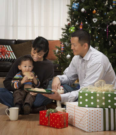 Asian family eating cookies next to Christmas tree