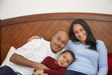 Mixed race boy lounging in bed with parents