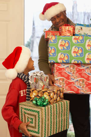 grampa: African grandfather and grandson carrying Christmas gifts