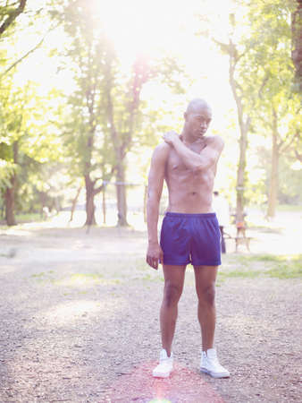 bare chest: African man standing in park with bare chest