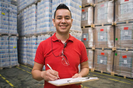 hispanic students: Hispanic man with clipboard smiling in warehouse LANG_EVOIMAGES