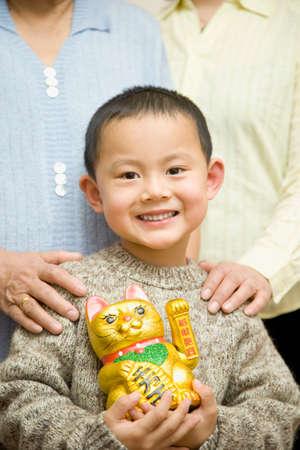 beckoning: Chinese boy holding beckoning cat LANG_EVOIMAGES