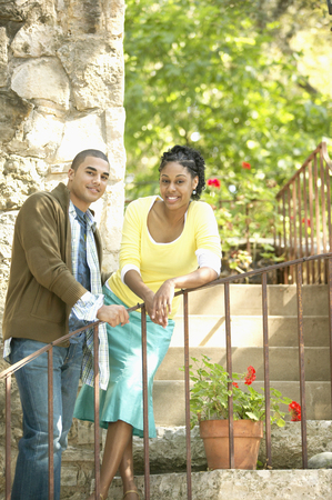 Portrait of a young couple standing together leaning on a railing Stock Photo