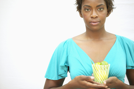 Portrait of a young woman holding a glass filled with kiwi fruit Stock Photo