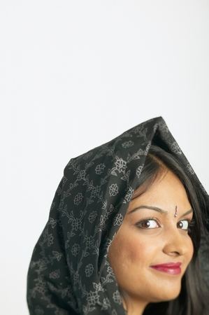 Portrait of a young woman with a scarf over her head smiling