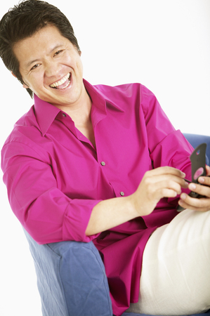 Portrait of a adult man sitting holding a hand held device smiling