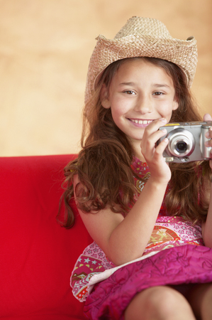 Young girl sitting on a couch holding a camera Stock Photo - 107927084
