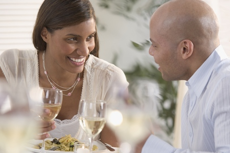 Young couple talking to each other eating food