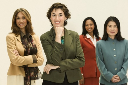 Group of young businesswomen standing together looking at camera smiling Stock Photo