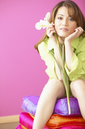 Young woman sitting holding a flower stalk