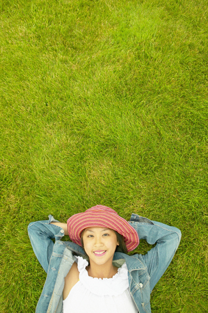 High angle view of a teenage girl lying on a lawn