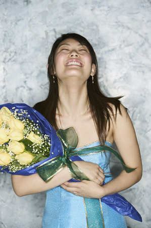Young female beauty contest winner holding a bouquet of flowers looking up Stock Photo