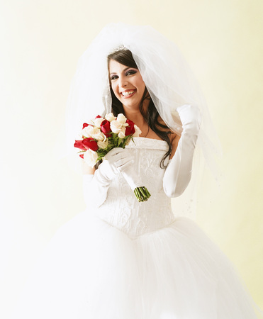 Portrait of a young woman wearing bridal outfit holding a bouquet of roses