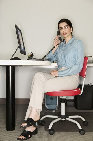 Frau, die an einem Schreibtisch in einem Büro sitzt Standard-Bild