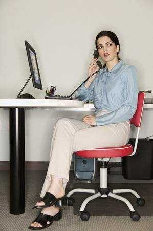 Woman sitting at a desk in an office Reklamní fotografie